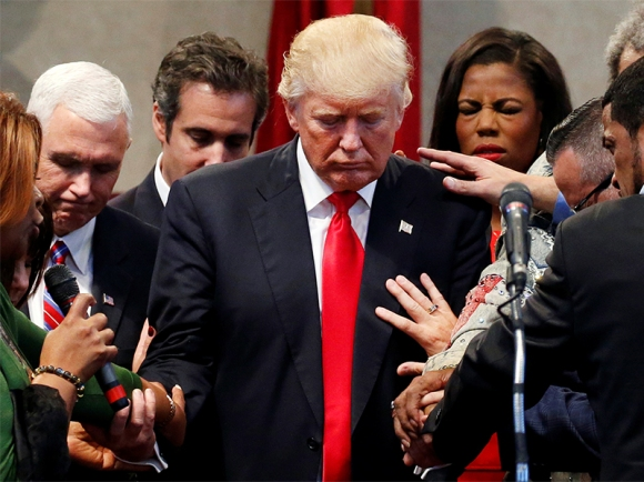 Members of the clergy lay hands and pray over Republican presidential nominee Donald Trump at the New Spirit Revival Center in Cleveland Heights